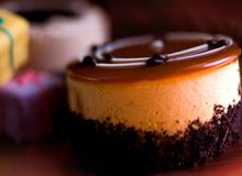 Cupcake with pastry. Demi cake mousse Cupcake with caramel topping and petits fours in the background stock photography