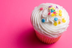 Cupcake on Pink. A cupcake with icing and sprinkles on a pink background Stock Image