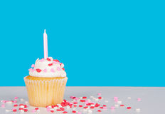 Cupcake with pink candle and heart sprinkles Royalty Free Stock Photos