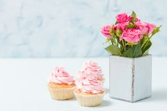 Cupcake with pink cream decoration and pink roses in retro shabby chic vase. Blue pastel horizontal banner with copy space for congratulation poster, greeting Royalty Free Stock Photo