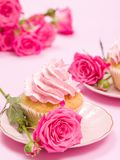 Cupcake with pink cream decoration and roses on pink pastel background. Cupcake with pink cream decoration and roses on pink pastel background - romantic Royalty Free Stock Photo