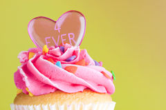 Cupcake with pink frosting and heart Royalty Free Stock Photography