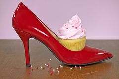 Cupcake in red high heel shoe. Cupcake with pink frosting and sprinkle beads in red high heel shoe on wood Stock Images