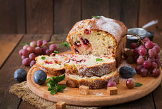 Cupcake with plums and grapes. Royalty Free Stock Images