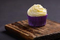 Cupcake in purpere omslag op houten raad op donkere steenlijst Minimaal concept De ruimte van het exemplaar stock afbeelding