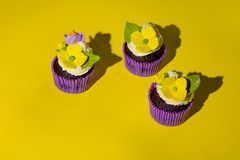 Cupcake in purple wrap on solid yellow background with strong shadow. Pop art. Trendy funky minimalist style. Food fashion poster, cakes, minimalism, design stock photo