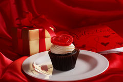 Cupcake with a red heart on top and gifts in boxes on red satin Stock Images