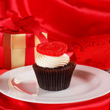 Cupcake with a red heart on top and gifts in boxes on red satin Stock Image