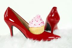 Cupcake in red high heel shoe. Cupcake with pink icing and sprinkles in red high shoe on white fur Royalty Free Stock Photography
