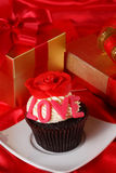 Cupcake with a red rose on top and gifts in boxes on red satin b Royalty Free Stock Photography