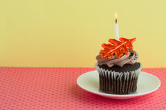 Cupcake on a Saucer with a Candle Royalty Free Stock Images