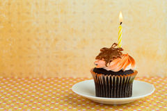 Cupcake on a Saucer with a Candle Royalty Free Stock Photo