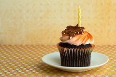 Cupcake on a Saucer with a Candle Stock Image