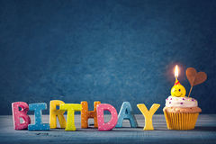 Cupcake with smiley candles. And colorful balloons Royalty Free Stock Images