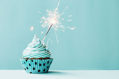 Cupcake with sparkler. Against blue stock image