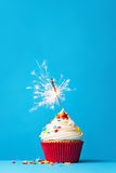 Cupcake with sparkler on blue Royalty Free Stock Photos