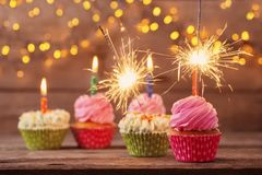 Cupcake with sparkler on old wooden background. The cupcake with sparkler on old wooden background Royalty Free Stock Image