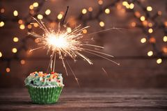 Cupcake with sparkler on old wooden background. The cupcake with sparkler on old wooden background Stock Photo