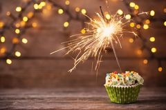 Cupcake with sparkler on old wooden background stock image