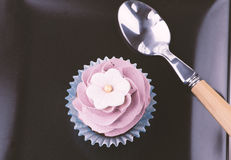 Cupcake and spoon on black dish Stock Image