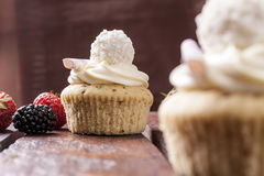 Cupcake with strawberries in studio. Jam cupcake with mascarpone cream cheese topping strawberry on table in studio Royalty Free Stock Images