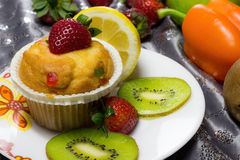 Cupcake with strawberry topping. Picture of a Cupcake with strawberry topping and various fruits and vegetables as background Royalty Free Stock Photography