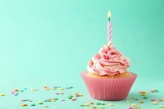 Cupcake. Tasty cupcake with candle on green background Royalty Free Stock Image