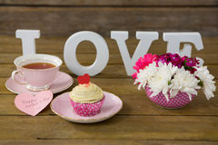 Cupcake, tea, flower vase and happy mothers day greetings card in tray. On wooden plank Royalty Free Stock Photos