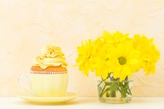 Cupcake with tender yellow cream decoration and bouquet of chrysanthemum in glass on yellow pastel background. Stilllife and minim. Cupcake with tender yellow Stock Photo