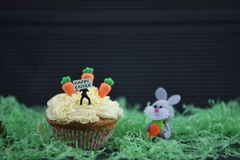Cupcake topped with a miniature person figurine holding a sign for happy Easter with decorations of a bunny rabbit and carrots. Rustic Easter time decorations Stock Photography