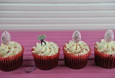 Cupcake topped with a miniature person figurine holding a sign for happy with some egg decorations. Easter time decorations of pink speckled eggs. With delicious royalty free stock images