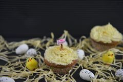 Cupcake topped with a miniature person figurine holding a sign indicating i love Easter with some decorations. Rustic Easter time decorations with some straw and stock photos