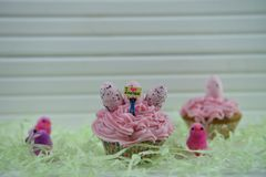Cupcake topped with a miniature person figurine holding a sign indicating I love Easter with some decorations. Easter time table decorations of fluffy pink and stock photography