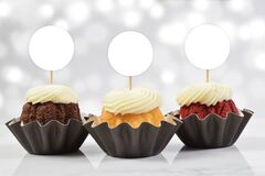 Cupcake Toppers Mockup with Three Gourmet Cupcakes and a Bokeh Patterned Background