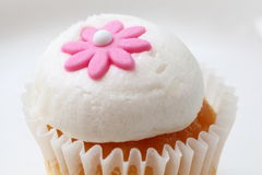 Cupcake topping. Close-up of a cupcake decorated with a tiny pink flower on its creamy topping - neutral background Stock Photography