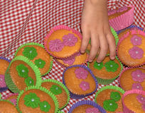 Cupcake treat. Hand of a child grabbing a cupcake treat from a colorful basket royalty free stock photos