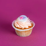 Cupcake for Valentine's Day with hearts on top of whipped cream on colourful background. Stock Photos