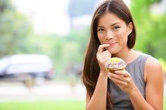 Cupcake - vrouw die cupcakes in New York eten stock afbeelding