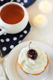 Cupcake with whipped cream and cherry Stock Photo