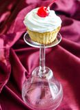 Cupcake with whipped cream and maraschino cherry Royalty Free Stock Photography
