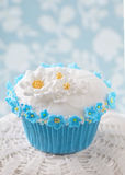 Cupcake with white and blue flowers Stock Images