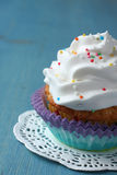 Cupcake with white cream icing and candy sprinkles Royalty Free Stock Photo