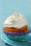 Cupcake with white cream icing and candy sprinkles Royalty Free Stock Images