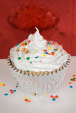 Cupcake with white frosting and sprinkles Royalty Free Stock Images