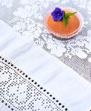Cupcake on a white lace tablecloth Royalty Free Stock Images