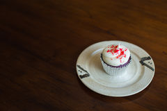 Cupcake on wooden table. Cupcake on wood brown table. White cupcake on dish stock photography