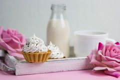 Cupcake with cream decorated with chocolate chips and coffee cu. Cupcake on a wooden tray with rose flowers, milk bottle and coffee cup, romantic breakfast on a Royalty Free Stock Photo