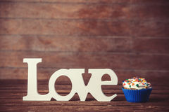 Cupcake and word Love. On wooden table Royalty Free Stock Photo