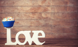 Cupcake and word Love. On wooden table Stock Photography