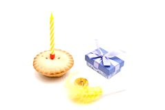 Cupcake with yellow birthday candle, whistle and gift on white Stock Photography